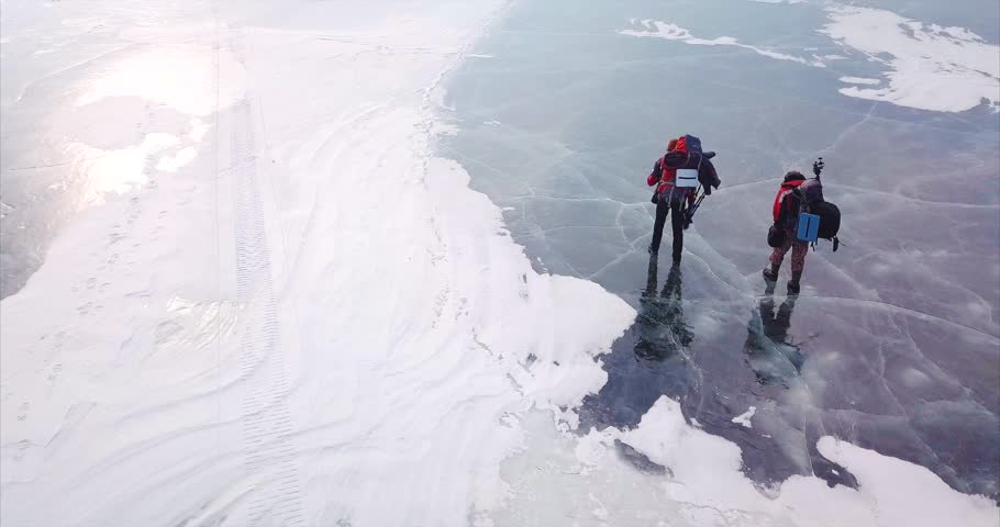 Aerial view of frozen lake and two photographers of wild nature with photography equipment walk on slippery ice. Lake Blagodatnoe in the Sikhote-Alin Biosphere Reserve in Russia