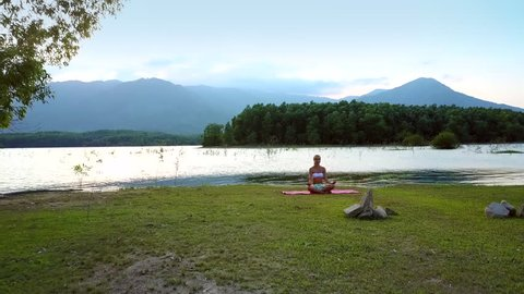distant view girl changes yoga poses sitting on lake bank against pictorial hills and green opposite bank