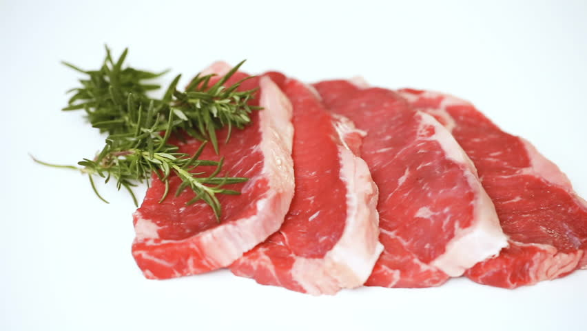 Raw New York strip steaks on a white background. | Shutterstock HD Video #1014000674