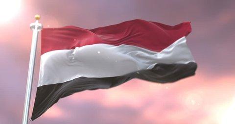 Flag of Yemen waving at wind in slow at sunset, loop