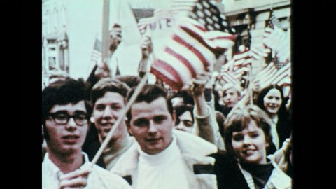 1960s: People wave flags, hold signs during protest. Group of people sit on floor, clap, stand up, hold up peace signs. Man stands on stage at microphone.