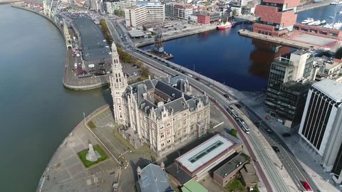 Aerial footage of Belgium Antwerp classic building Loodsgebouw located in old city center Schipperskwartier also showing old steamcrane and modern buildings in background 4k high resolution footage