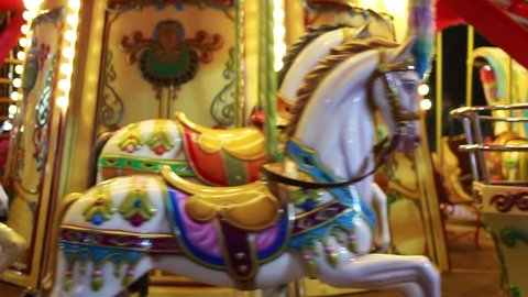 Bright red and golden carousel with horses and bright glowing lights turning around without passengers in darkness of night. Real time full hd video footage.