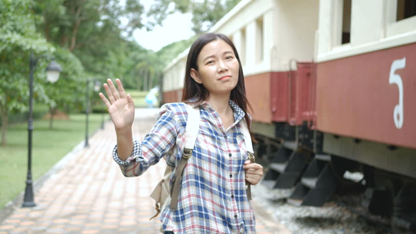 4K. Asian tourist woman waving hands to say goodbye in departing train at train station. bye bye