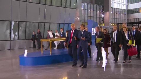 2018 - U.S. President Donald Trump moves through a crowd at the NATO summit conversing with French President Emmanuel Macron.