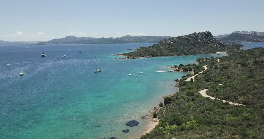 Aerial view flying over amazing turquoise water, towards green mountain at Sardegna, Italy.