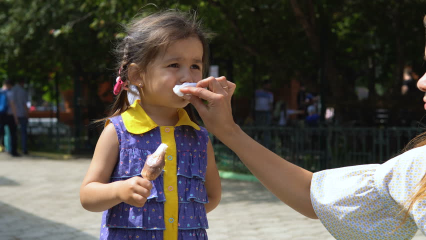 Mom wipes his little daughter's face, soiled with ice cream. In the background a public park.