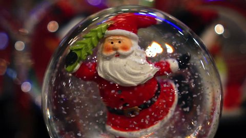 Close up of Santa Claus inside a snow globe, in slow motion