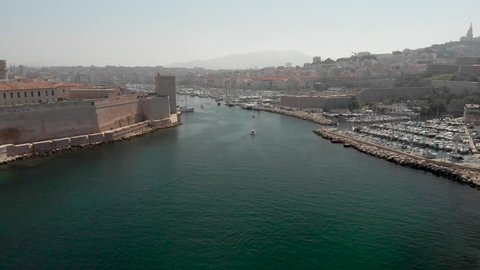 Flying into the old port of Marseille in aerial drone shot. French marina with yachts and boats traveling by historic castle and phare de sainte marie lighthouse into cafetiere.