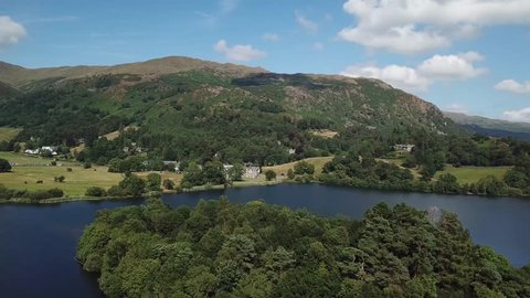Aerial drone footage flying over a peaceful tree filled island in the middle of a lake   The Lake District   4K