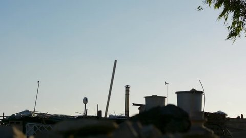 Chimney, Water Tanks and Wind Vane of a small room in the countryside of Malta.
