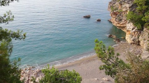 Beautiful sunrise at charming deserted rocky beach in Turkey. Top view from high rock of bright blue sea water, green plants and huge stones. Real time full hd video footage.