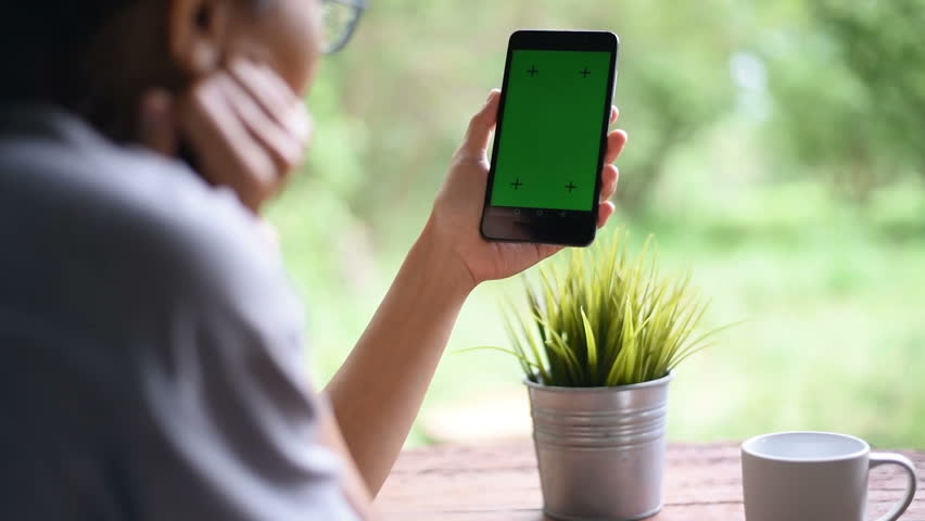 An over the shoulder shot of a young woman video chatting outside with green screen on her smart phone. | Shutterstock HD Video #1014138194