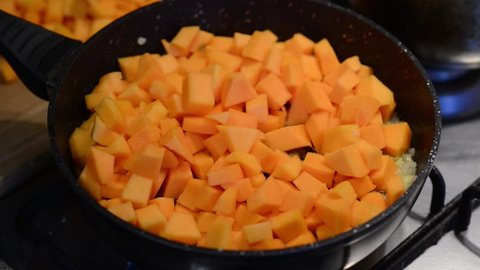 Cooking pumpkin soup. Frying pan with butter chopped onion and cubed pumpkins. Healthy food, diet. Homemade meal with autumn pumpkin. Preparing traditional pumpkin soup