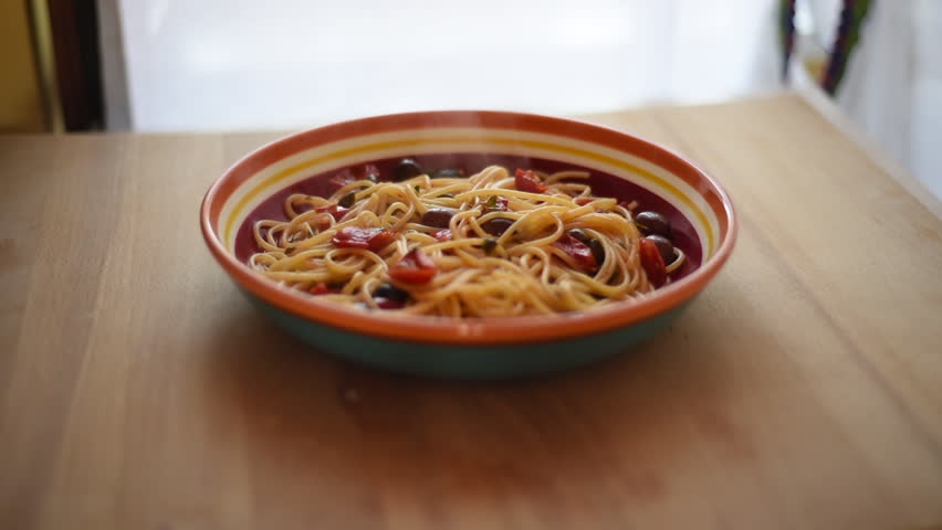 A plate of spaghetti with cherry tomatoes, olives and capers. A very good Italian summer food.