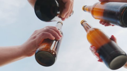 A group of friends clink glasses with beer bottles against the sky, the lower camera angle