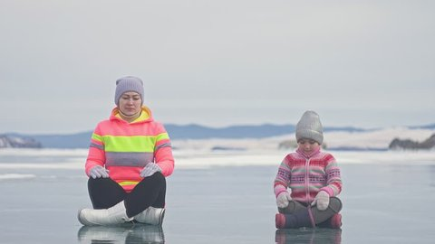 Family is training practice yoga in winter. Woman is do stretching and meditation on ice in nature. Mother and daughter practices yoga on ice in cracks. Girls do sport fitness in outdoor. Background