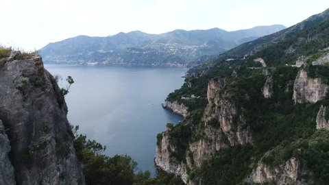 Aerial footage of rough and inaccessible Amalfi coastline moving through rock formation revealing rest of the beautiful coastline and far distant view of the Italian country near Naples 4k quality