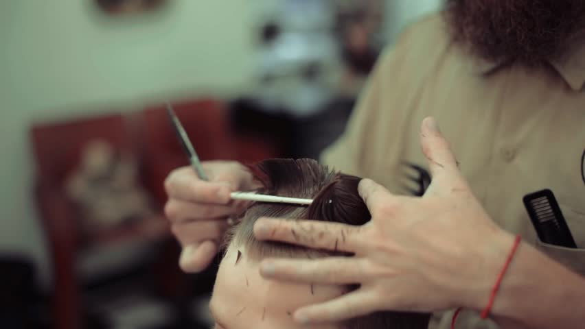 Men's haircut in barbershop. Barber makes a hairstyle and styling a client. Scissor cutting. Hair Care. | Shutterstock HD Video #1014167864