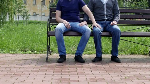a man sits on a bench in the city to him another man approaches, they stroke one another on the leg, take hands and leave, gays, homosexuality, same-sex marriage