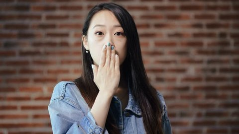 Ashamed or embarrassed Asian young woman, brick wall on background. Negative human emotion, facial expression, body language perception concept. Closeup portrait woman looking ashamed or shy.
