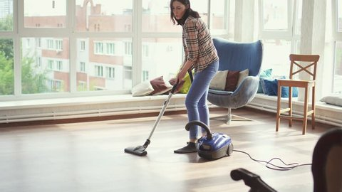 Young housewife dancing and vacuuming