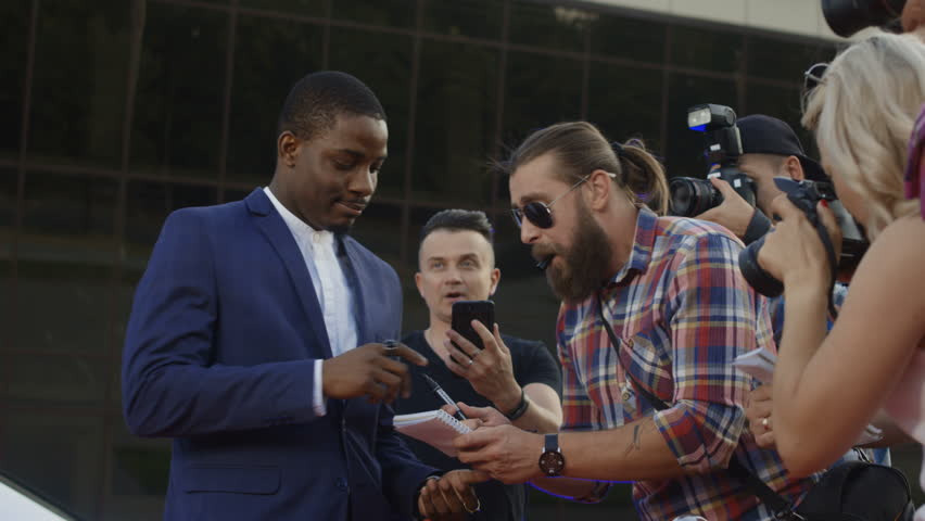 Ethnic celebrity man giving autographs to people on red carpet and makes photos #1014214064