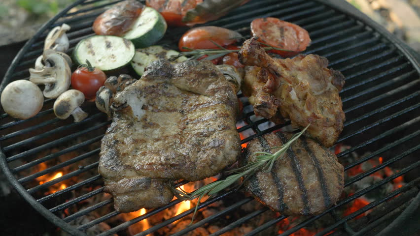 Assorted meat with grilled vegetables and rosemary sprigs, in the foreground hamburger cutlet, steak on the bone, ribs, grilled vegetables, zucchini, tomatoes, mushrooms, garlic head, chef turns the | Shutterstock HD Video #1014216164