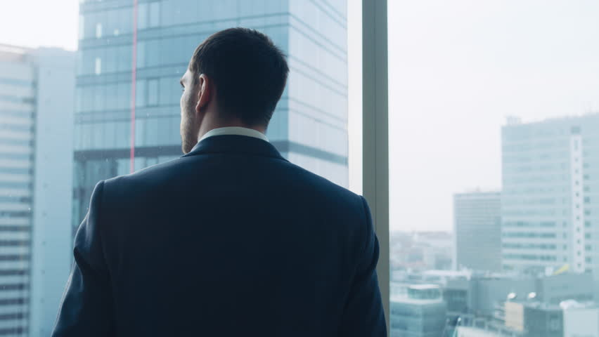 Medium Shot of Successful Businessman wearing a Suit Standing in His Office, Contemplating Next Big Business Deal, Looking out of the Window. Shot on RED EPIC-W 8K Helium Cinema Camera. | Shutterstock HD Video #1014231614