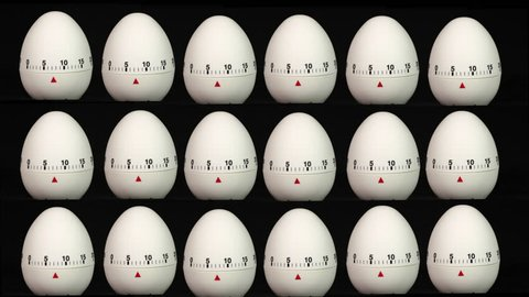 White kitchen egg timers the same size in rows on a black background counting down to zero time lapse.