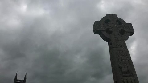 Celtic cross on a sky with clouds in Drumcliff, Ireland. Drumcliff Churchyard.Drumcliffe is best known worldwide as the final resting place of the poet William Butler Yeats