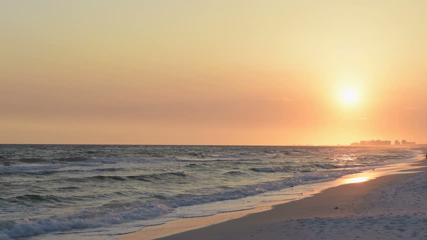 Dreamy pastel orange sunset in Santa Rosa Beach, Florida with Pensacola coastline coast cityscape skyline, man walking, in panhandle with ocean gulf of mexico waves washing in slow motion