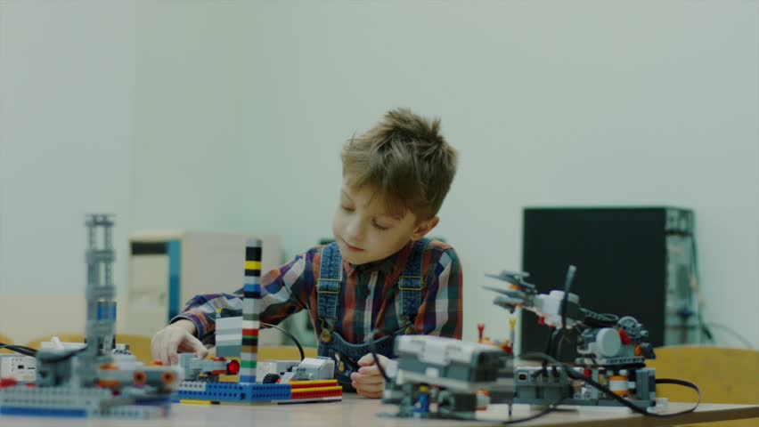 Young talented boy is in the engineering club working with robots. Lego robots on the table. Modern technologies. Boy playing indoor. | Shutterstock HD Video #1014275204