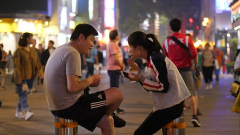 GUANGZHOU, CHINA - MARCH 16, 2018: Young Unidentified Asian Couple sit with ice cream in middle of pedestrian street, lively area at night time. People pass by, bright Beijing Lu shopping area