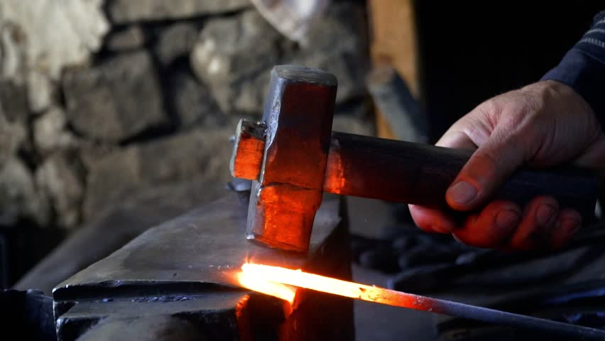 The blacksmith manually forging the molten metal on the anvil in smithy with spark fireworks. Blacksmith forging metal in slow motion. 4K