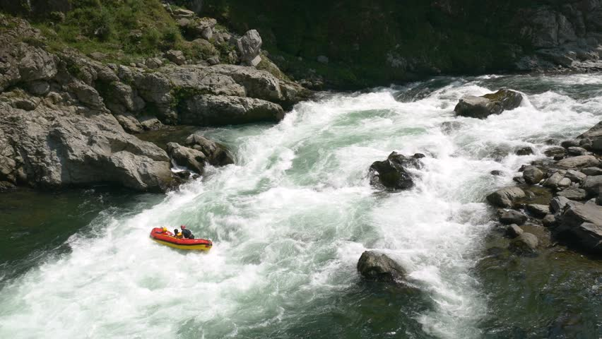 Three rafters battle the whitewater on the Yoshino River in Tokushima Japan with a final cheer