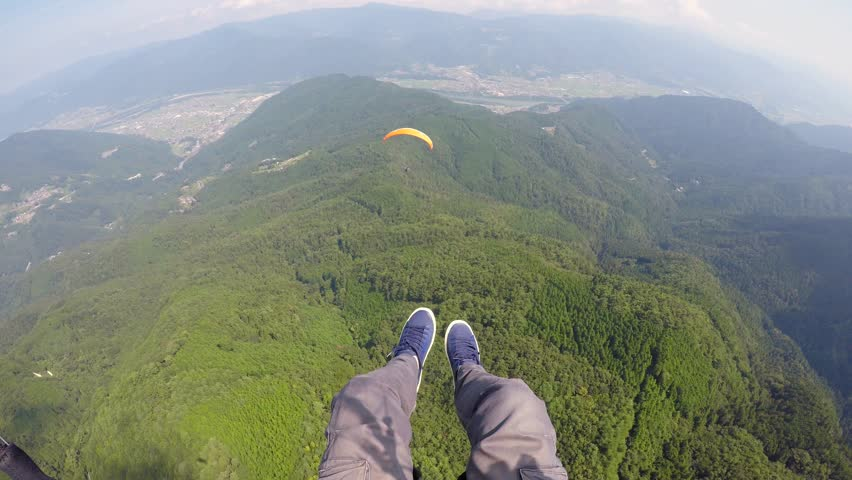 Solo Paraglider flies above a tandem glider in Japan in Summer
