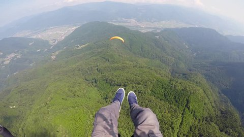 Solo Paraglider flies above a tandem glider in Japan in Summer