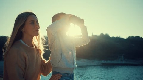 Happy Mother and son looking through binoculars on summer day at sunset on a sea background