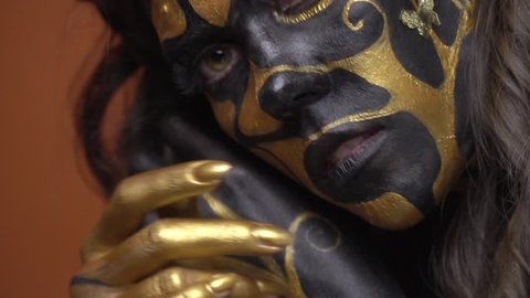 Mysterious woman in black and gold body art posing on camera, close up