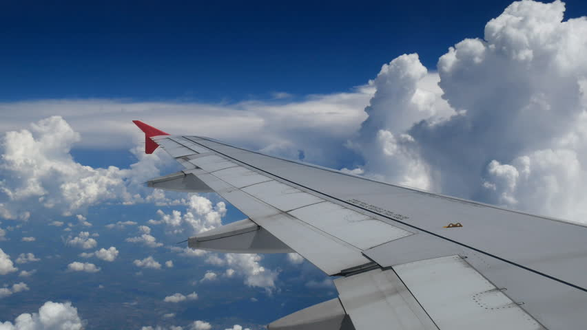4K footage airplane flight. wing of an airplane flying above the white clouds and blue sky. beautiful aerial view from the window of the plane on travelling time by aircraft. holiday, vacation time | Shutterstock HD Video #1014344864