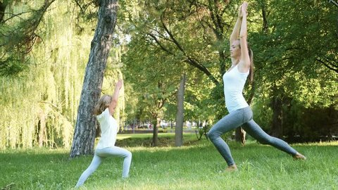 Young sporty mother doing yoga exercise with her little cute daughter in slow motion. Woman with child train in a green park. Helthy lifestyle family concept.