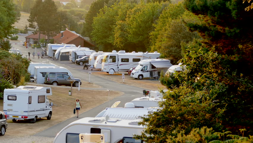 NORFOLK, ENGLAND, JULY 24TH, 2018: During a long UK heatwave, campers walk through a peaceful campsite of parked caravans and motorhomes, surrounded by trees, in the early evening.