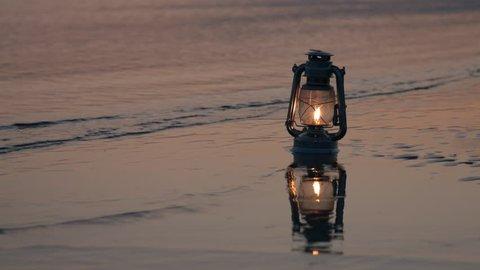 Old vintage kerosene lantern on beach at sunset