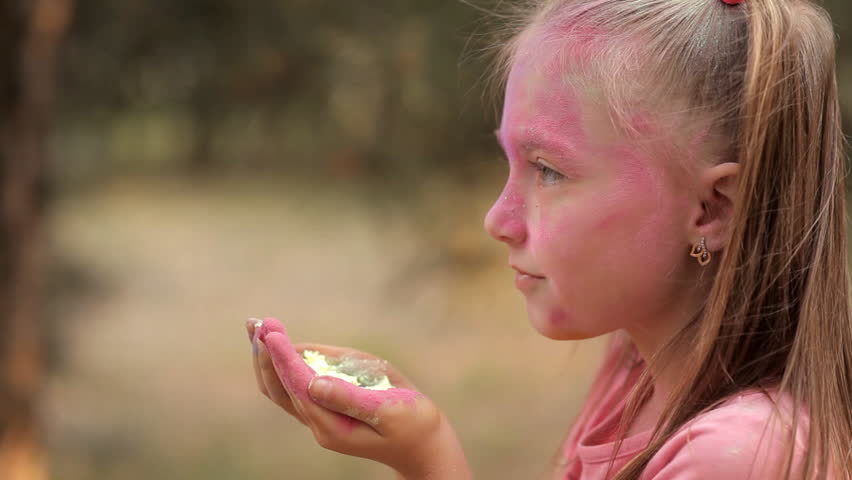 The girl blows off colored powders from her hands. Holi Festival | Shutterstock HD Video #1014406874