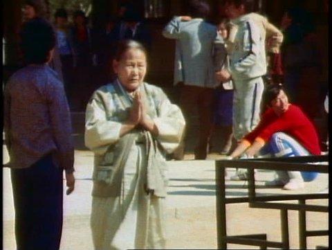 PUSAN, SOUTH KOREA, 1982, Buddha Land Temple women walks through courtyard, bows