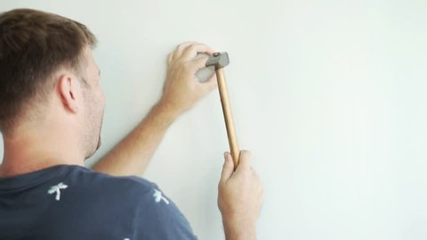 a man is standing by the wall and hammering a nail with a hammer. He knocks on the nail with a hammer, the nail enters the syten.