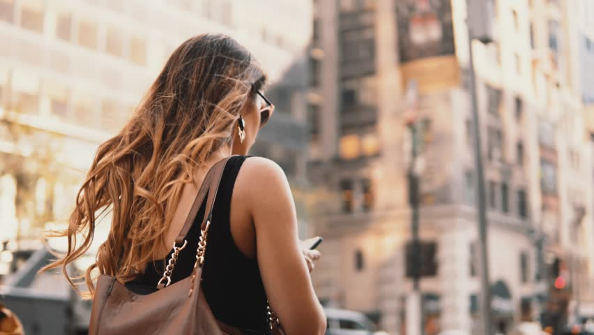 Young beautiful woman walking in downtown of New York, America, looking around and using smartphone. | Shutterstock HD Video #1014477284