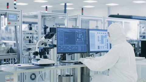 In Laboratory Over the Shoulder View of Scientist in Protective Clothes Doing Research on a Personal Computer. Modern Manufactory Producing Pharmaceutical Items.