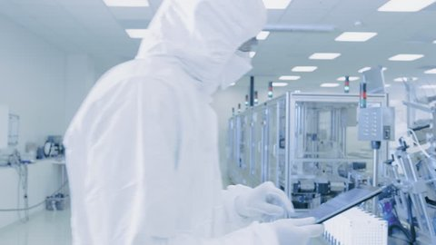Scientist Using Digital Tablet Computer and wearing Protective Suit walks through Manufacturing Laboratory with Modern Industrial Machinery.